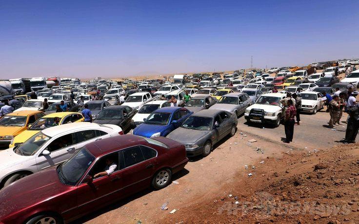 イスラム教スンニ派の過激派「イラク・レバントのイスラム国(ISIL)」率いる武装勢力によるイラク第2の都市モスル(Mosul)制圧を受け、同国北部クルド人自治区の首都アルビル(Arbil)から約40キロ西方のAski kalakの検問所に押し寄せた避難民たちの車(2014年6月10日撮影)。(c)AFP/SAFIN HAMED  ▼11Jun2014AFP|過激派掌握のイラク・モスルから約50万人脱出 http://www.afpbb.com/articles/-/3017430 #Erbil #Arbil #Irbil #Aski_kalak