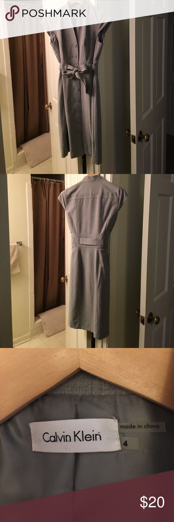 Calvin Klein Dress This is a professional gray dress that hits at the knee. It wraps at the waist to give your figure definition. Looks great with black pumps or kitten heels. Calvin Klein Dresses