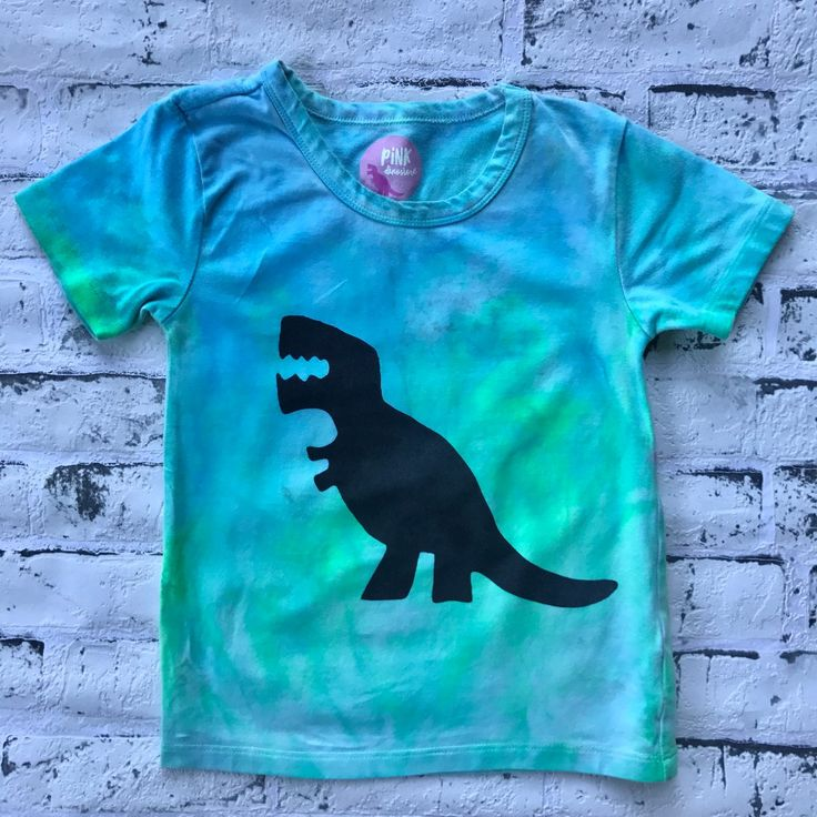 Made for those of you who aren't afraid of colour, these tees are unisex and on premium stock. They come in three amazing colour schemes, Sunrise, Hyper Bomb and Ocean. Each one is hand dyed by me, making it individual and unique just like your roarsome kid!   Blue & Green hand dyed shirt with screen printed trex dinosaur shirt for kids. Tie Dyed