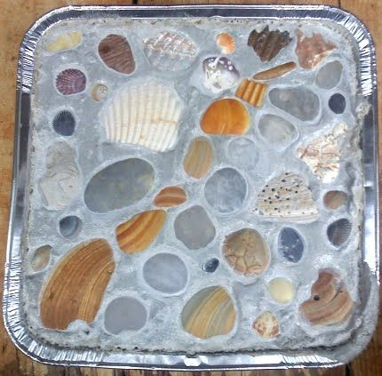 Mix up a batch of mortar (which is cement mixed with an aggregate), pour it into a mold (here a foil pan was used), then decorate with shells, sea glass or beach pebbles, and let dry. Easy!