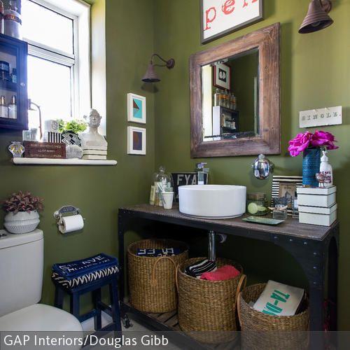 Die drei Bastkörbe dienen als lässige Aufbewahrungsboxen. Zusammen mit dem modernen Waschbecken in Rundform und Waschtisch, Wandspiegel und Wandleuchten im…