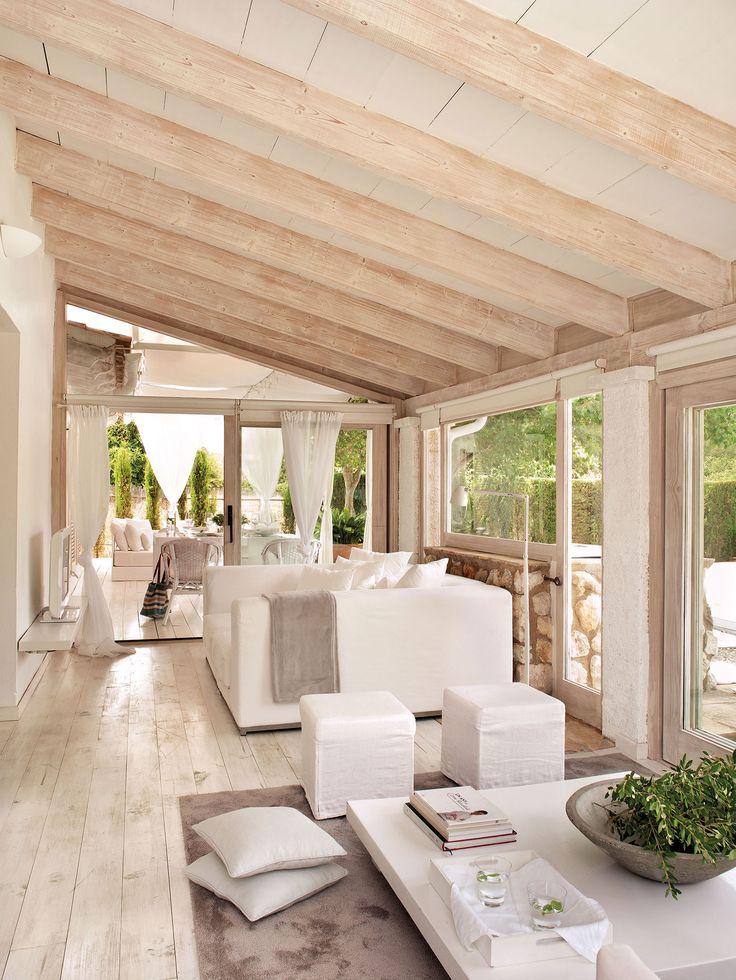 Salón actual en blanco con grandes cristaleras al jardín, suelo de madera y vigas decapadas