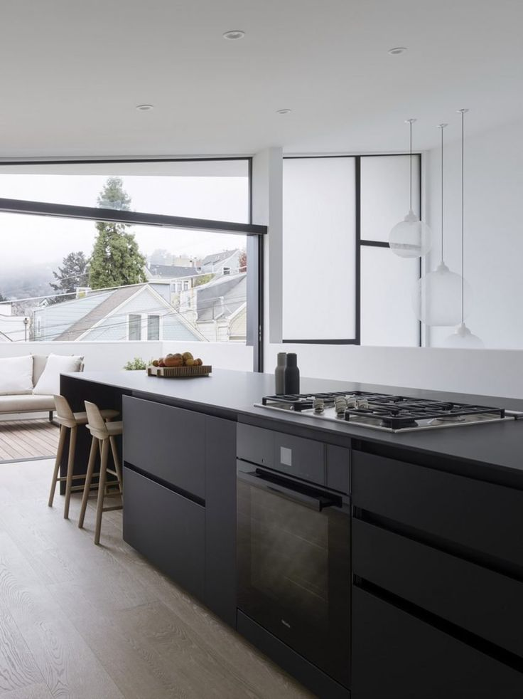 Occupying the front portion of the top floor is the kitchen, which opens onto an outdoor deck. Wide, wooden stairs lead down to the living room, which also opens onto a terrace, providing sweeping views of the city.
