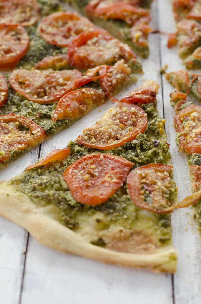 Vegan Pesto Pizza! You'll never guess this pizza was dairy-free! Pumpkin seed pesto topped with sliced tomatoes then roasted to perfection and topped with homemade vegan parmesan cheese! You've gotta try this pizza, even omnivores loved this one.   www.delishknowledge.com