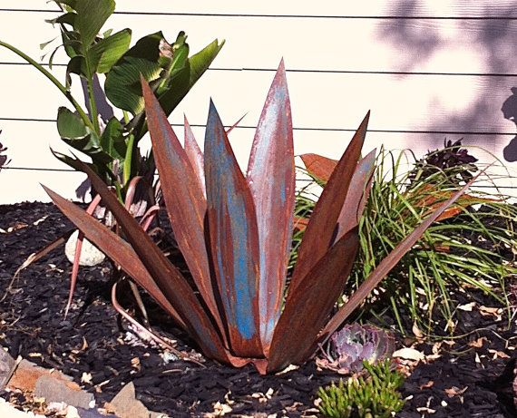 This is a 2 foot tall rusty blue Tequila agave plant, made of steel with blue high lights in contrast with the rusty steel. This tequila plant will brighten up any space you place it in. This particular agave has no base to give it a look as if its growing from out of the ground. At its base it is 10x10 inches wide. These are hand made to order so each plant will vary slightly.