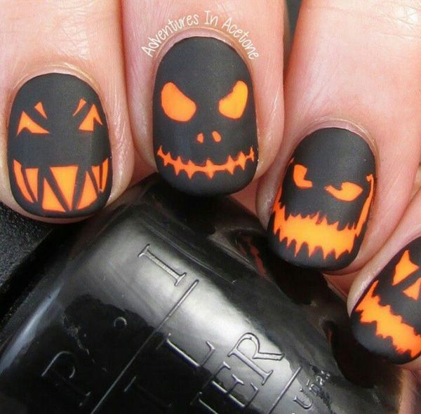 Creepy pumpkin heads Halloween nail art. Paint on scary pumpkin faces on your nails with black polish as your base coat and silhouette. Use an orange coat to paint on the details of the pumpkin faces.
