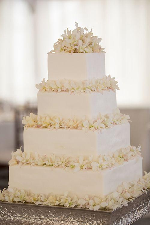 A four-tier white wedding cake with fresh orchids | Brides.com