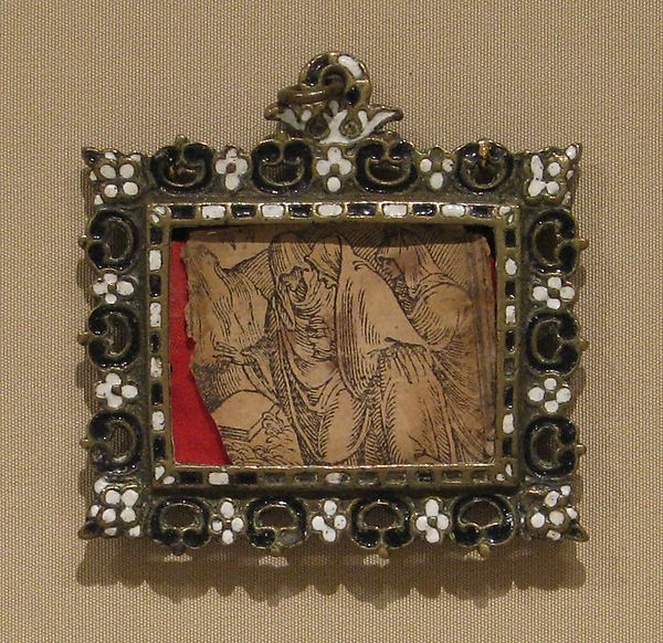 Although such framelike insignia were made in gold for the wealthier members of Marian confraternities, this one, of brass like the pair alongside it, must have belonged to a less properous adherent. Bearing the cipher of the Virgin on its front, behind the glass it still contains a fragementary engraving of the three Marys at the tomb