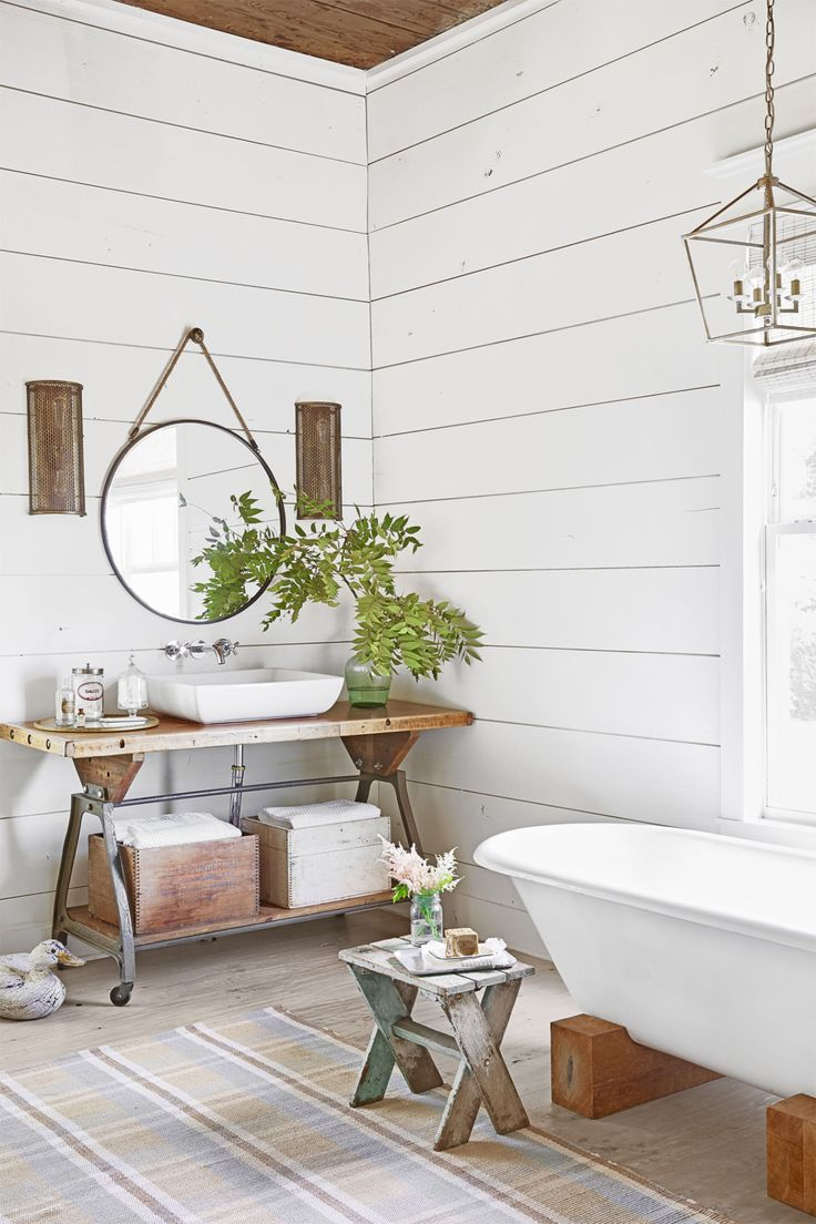 In the (new and improved!) master bath, a claw-foot tub sits on wood blocks. The vanity is simply an old work bench with a new vessel sink, while a simple salvaged doorknob became a smart substitute for a plain old nail.