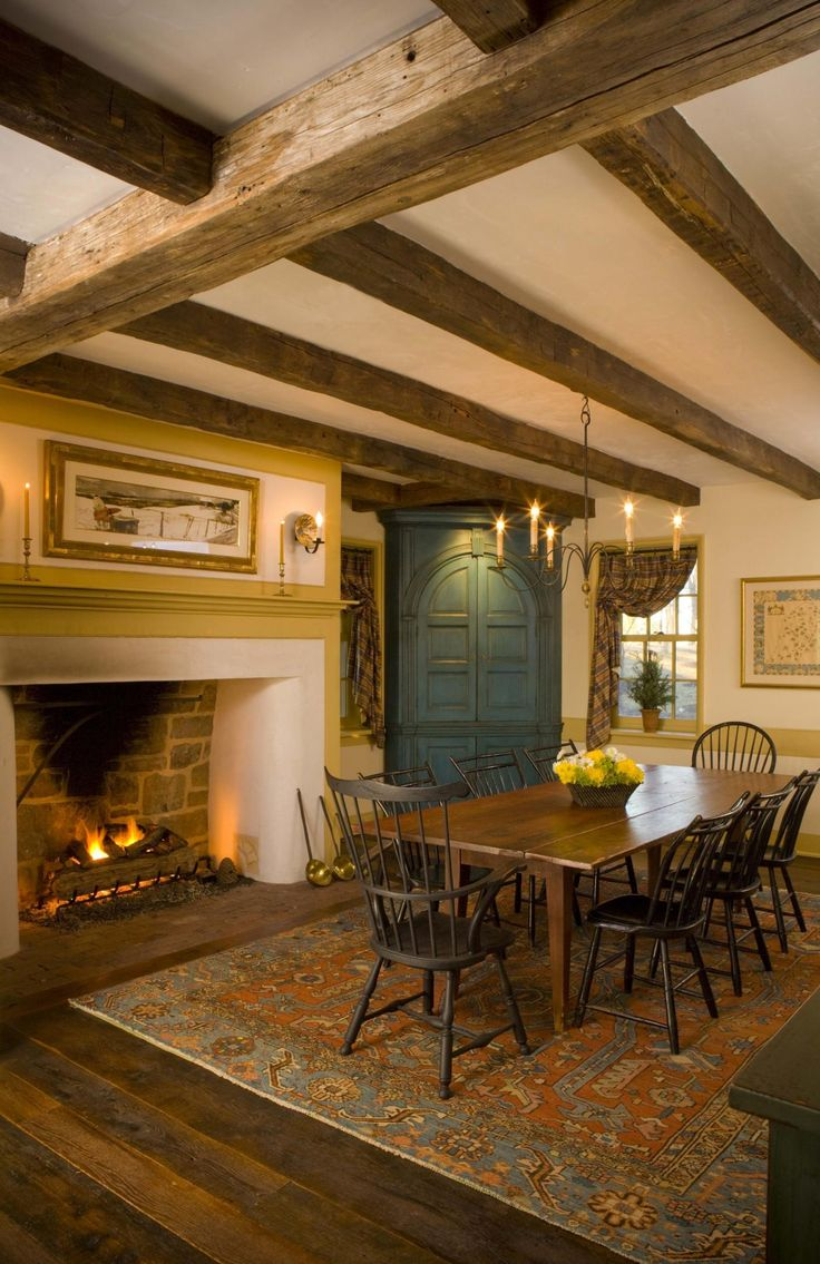 Декоративные балки на потолке столовой и настоящий камин создают колорит загородного  дома.