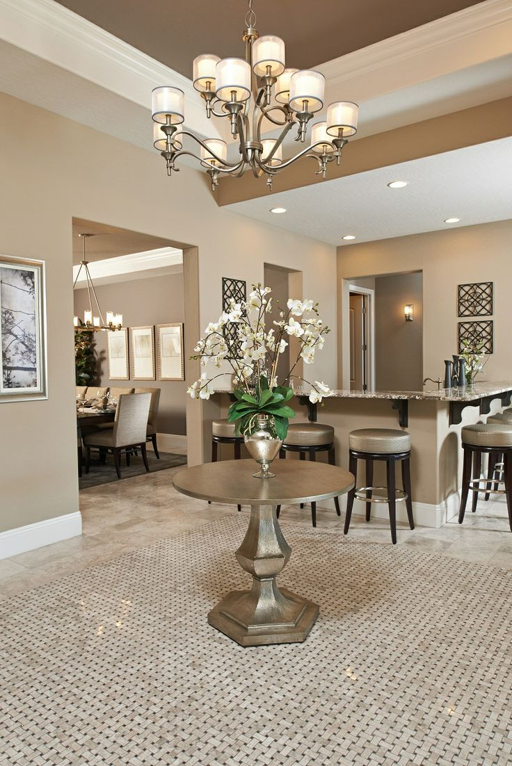 Tile flooring and metallic accents create a dazzling first impression in this foyer. | Reagan model home, Las Vegas