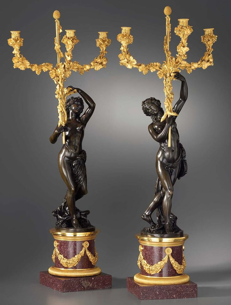 Pair of Louis XVI gilt and patinated bronze and red porphyry three-light figural candelabra