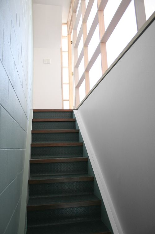 Contemporary translucent 'shoji' screen room divider to stair with industrial rubber flooring.