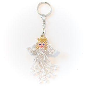 En skyddande #ängel, med vingar och guldkrona, skapad av massor av pyttesmå högglansiga #pärlor, flätade för hand till en mjuk figur. En #nyckelring som verkligen vakar över dina nycklar.