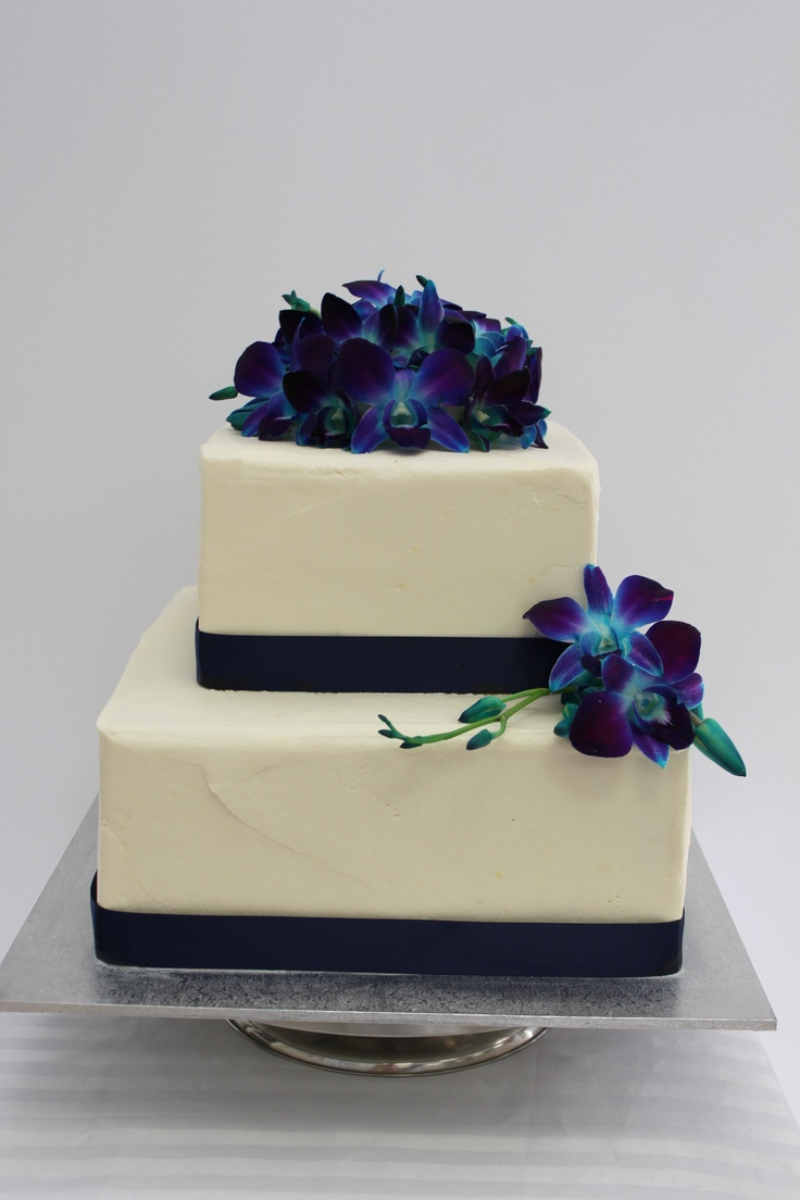 Natural buttercream two tier wedding cake with purple/blue singapore orchids.