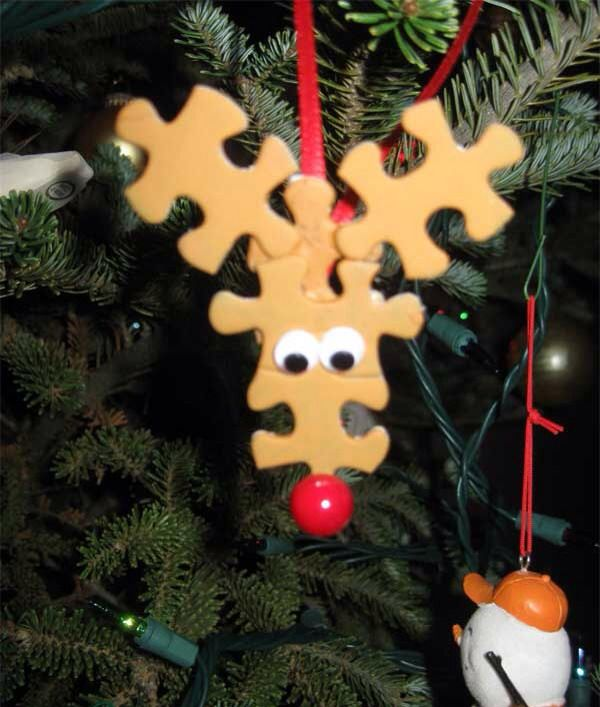 """Puzzled Reindeer Ornament ~ Spray paint 5 old puzzle pieces brown per reindeer.  Put two that go together for face; glue together and put two squiggly eyes at center.  Glue face to """"base"""" piece and add remaining two pieces for antlers.  Add red pompom for nose and glue ribbon to back to hang."""
