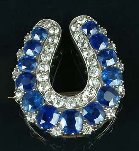 A sapphire and diamond brooch/pendant, c.1890, in the form of a lucky horseshoe.