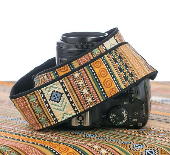 Camera strap with a southwestern design done up in stripes of different patterns. Colors include golds, browns, orange, yellow, turquoise, and green. All cotton fabrics are used on this 2 wide strap. Available in two lengths with a thin layer of padding. Back is black Outback fabric by Robert