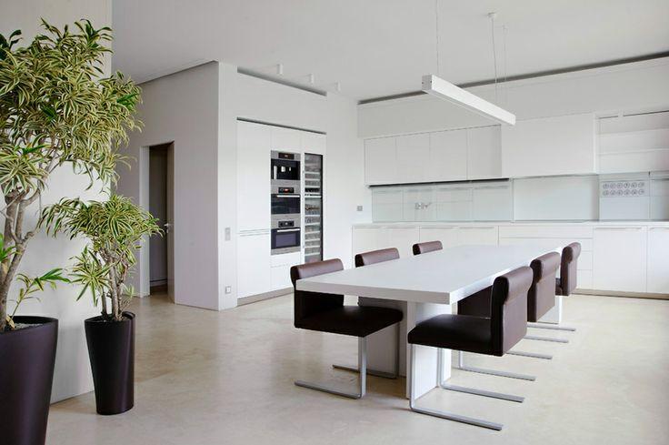 Строгая и лаконичная столовая в белых тонах с акцентными включениями черных деталей.
