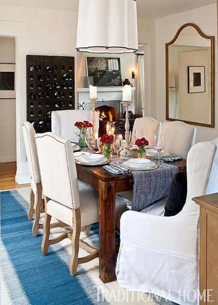 A Rustic Wood Table Paired With White Nailhead Trimmed Chairs Sits Atop Blue And Striped Rug In Cozy Casual Dining Room