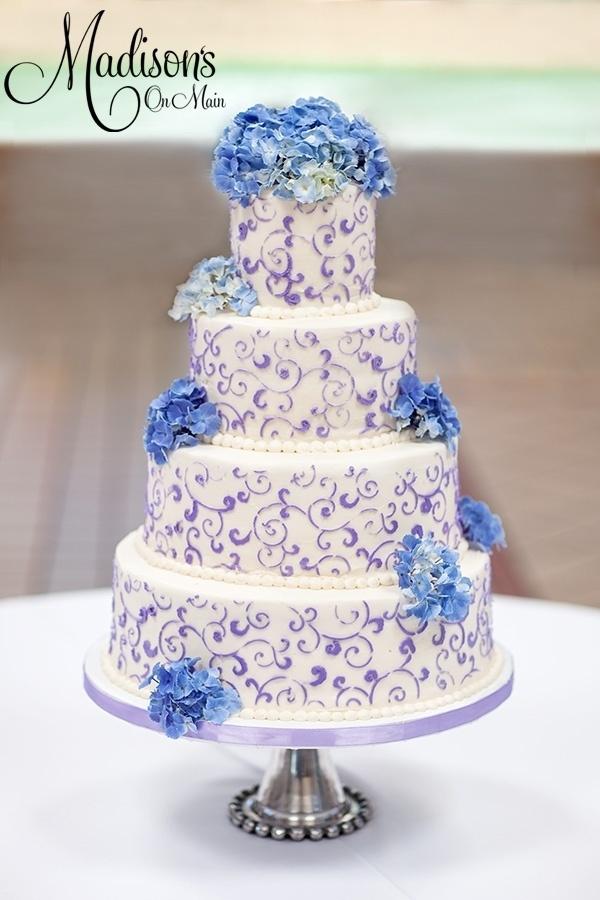 Buttercream wedding cake with Lavendar scrollwork and fresh hydrangeas. (Make it purple hydrangeas with pale pink scrollwork?)