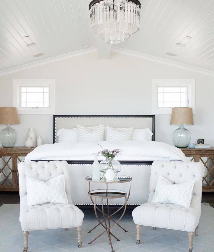 White master bedroom with glossy paneled ceilings | side chairs at foot of bed | white tufted bed with dark wood | airy light all white master bedroom