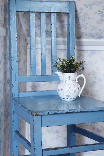 Sweet pale blue floral wallpaper, weathered blue chair and herbs in blue fluted pitcher