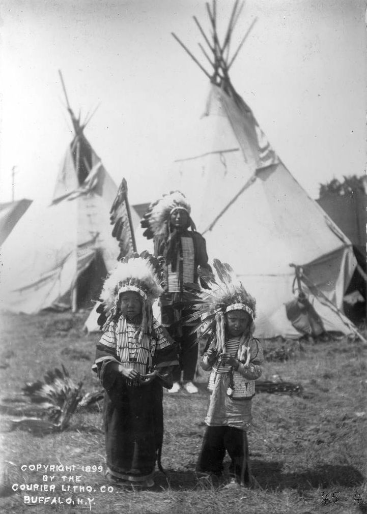 A Sioux man, probably Chief Iron Tail, stands behind two Native American children in a camp for Buffalo Bill's Wild West Show - 1899 (picture # 2)