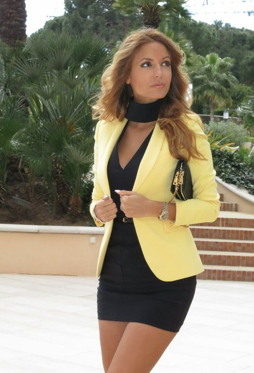 A belted black dress, yellow blazer, and a scarf to top of the ultra career chic ensemble.