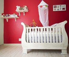 A girl's nursery with a cream and red colour scheme. The wooden cot coordinates with the choice of flooring.  #Nursery #interior #homedecor