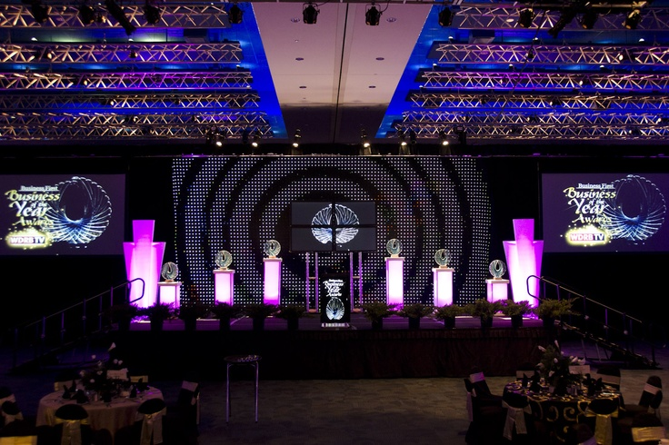 """Business First - Business of the Year in the Cascade Ballroom of the Kentucky International Convention Center featuring HD Video Projection on AV Stumpfl screens, 24' black velour drape, 16'x33' SoftLED Dynamic Video Drapery backdrop, 4x50"""" plasma displays configured as a mini video wall on truss towers and custom set pieces."""