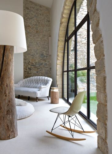 steel frame arched windows exposed stone walls white floor modern