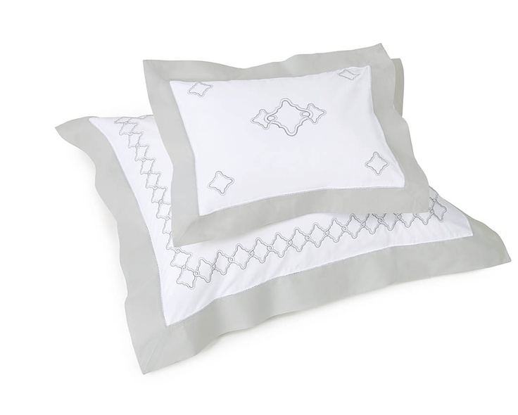 Quarto bedding in soothing Silver Sage hue is embroidered and finished with a contrast-color cuff.
