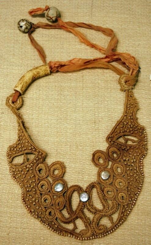1)dye granny lace w/ tea 2)attach ripped silk strips & beads 3)rub in dirt....voila! opera attire!