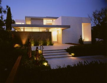 Notice how the architects have given the impression of a floating roof in this Los Angeles house. The windows are either large, focusing on a particular point of interest, or arranged in ribbons and mitered at the corners. The walls of the house appear massive and solid, like large blocks. The details are flush and smooth.
