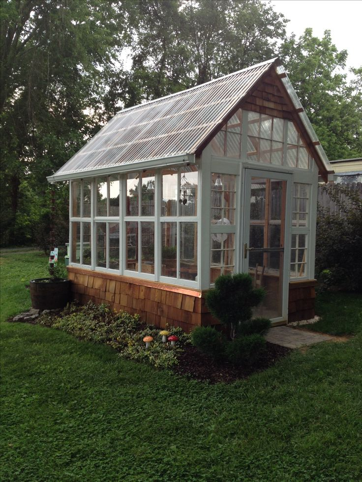 This is a 7 x 12 feet greenhouse made out of old windows, polycarbonate plastic roof panels and cedar shakes.