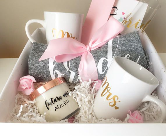 Beautifully designed engagement gift basket for the bride to be! This gift set is guaranteed to get her excited about the big day! Each gift set includes: 1- bride gray v-neck t-shirt with white matte script lettering (Loose fitting shirt, select size at check out) 1- Personalized