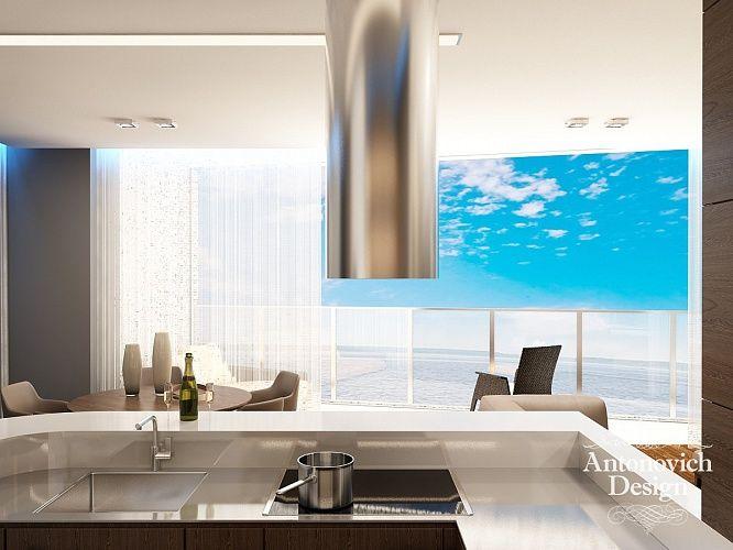 Барная стойка, над которой разместили оригинальную вытяжку в виде стальной трубы, ограничивает зону небольшой кухни. Ровные геометрические формы мебели в которой подчеркнуты скрытой подсветкой.
