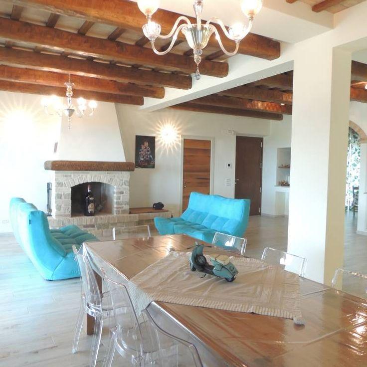 Ampio salotto con divani molto colorati e moderni in contrapposizione ad un ambiente rustico: Soggiorno % in stile % {style} di {professional_name}