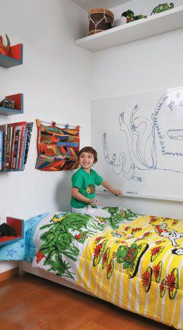 Crianças que adoram desenhar vão adorar ter um quarto como este, projetado pela arquiteta Clarissa Guimarães. Ao lado da cama, uma lousa branca permite brincar e soltar a imaginação quantas vezes quiser. Na cabeceira, um porta-trecos colorido serve para organizar brinquedos. Há prateleiras ao lado da cama e até rente ao teto, para ajudar na organização. Edredon Reino das Águas, da Tok & Stok.