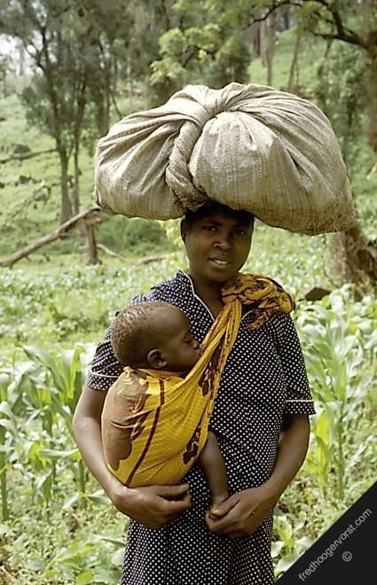 uganda mother child carrying heavy load on-her head her family garden food africa afrika voedsel moeder vrouwen landbouw vertical