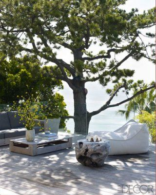 On the deck, a teak stool sits beside a chair by Paola Lenti; the sofa and cocktail table are by Sutherland.