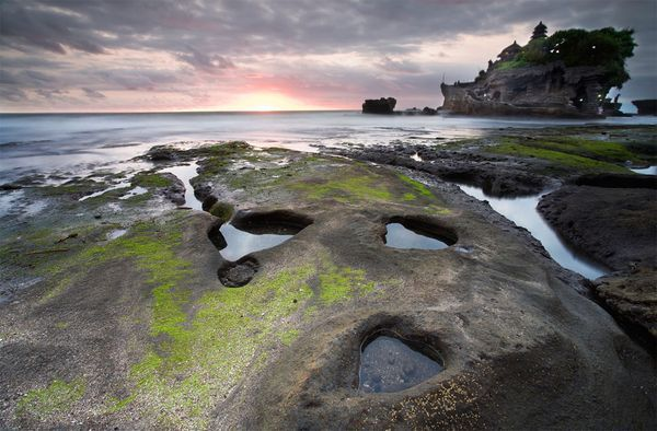 Tanah Lot in Bali in Indonesia is located on a huge rock amidst the sea.