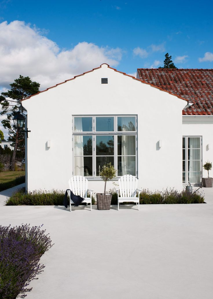White country house, red tile roof, pale pale grey windows and doors.