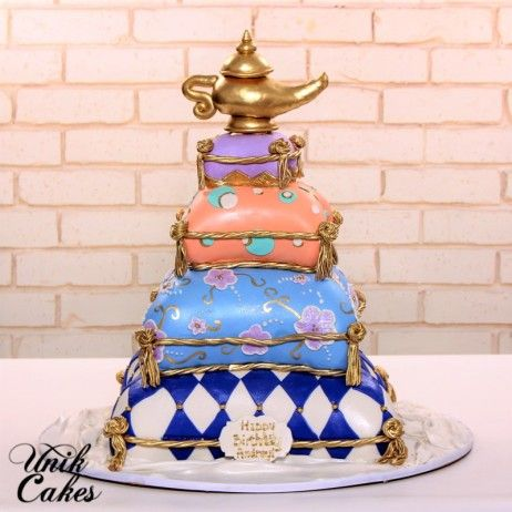 Moroccan themed birthday cake.  The cake was decorated in shape of pillows stacked one on top of another. Bottom tier decorated in royal blue diamond pattern. Next tier decorated in medium blue fondant, lilac applique and hand painted gold swirls. Third tier decorated in peach fondant, teal, gold and white polka dots. Top tier decorated in lilac fondant and golden pillow tassels and magic lamp of Aladdin.