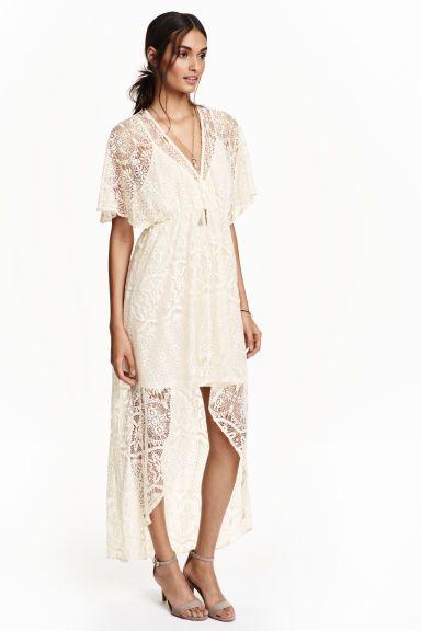 Robe en dentelle: Robe à encolure en V en dentelle ajourée. Modèle court devant et long sur l'arrière. Courtes manches papillon. Fond de robe cousu en jersey souple avec fines bretelles réglables.