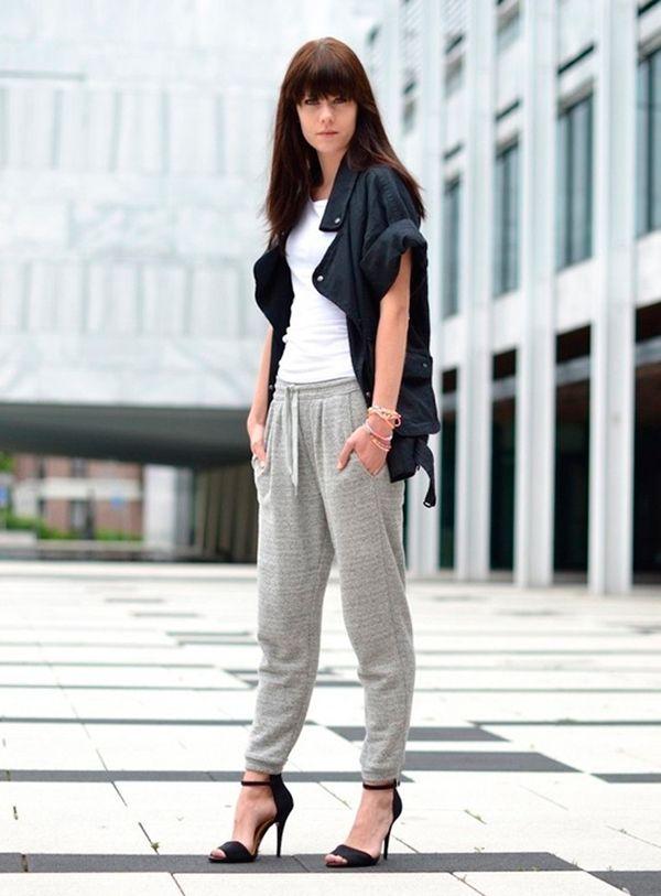 Foto de street style de look comfy com t-shirt branca, parka preta, calça de moletom cinza e salto preto