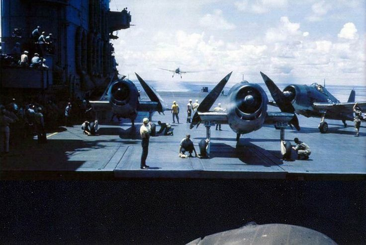 Grumman F6F Hellcat fighters sit with propellers running and wings folded on the flight deck of the aircraft carrier USS Saratoga (CV-3) during World War II.  (U.S. Navy Photograph.)
