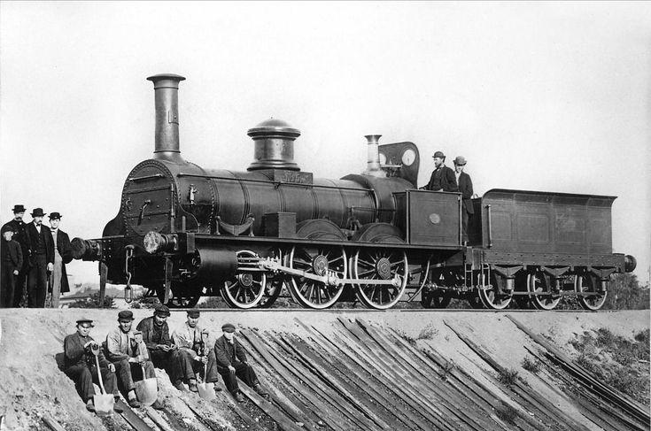 Svart-hvitt fotografi som viser lokomotivpå skinner. Arbeidere sitter i forgrunn, funksjonærer også til stede