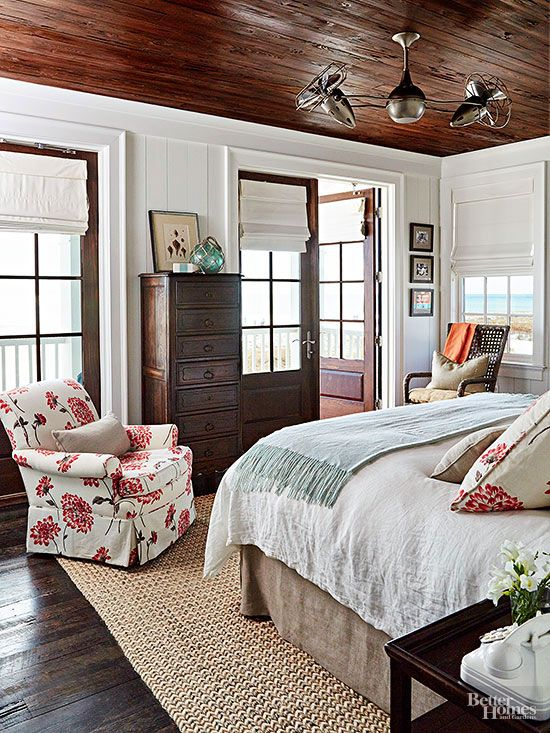 Prevent a cabin-style room from becoming too literal with a contemporary accent color. Here, a modern red floral pattern featured on several throw pillows and a cozy club chair balance a woven seagrass rug and crisp white siding.